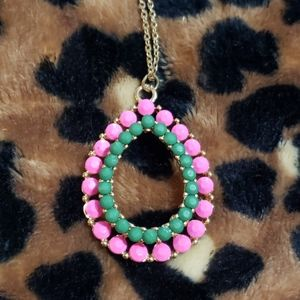 Gold tone necklace with pink and green pendent